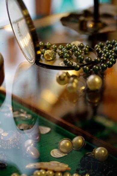 Lyxig femtiotalsextravaganza; skimmrande pärlor och spegeldosa.