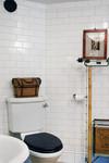 Sekelskiftesbadrum med väggar klädda med halftilekakel och tidstypiskt santitetsporslin.